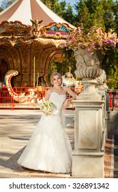Smiling bride near decorative sculpture in front of carousel