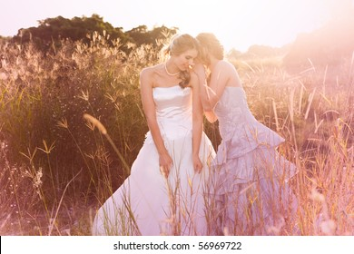 A smiling bride wearing a white wedding dress is listening to her bridesmaid in a rural landscape tell her a secret. Horizontal shot.