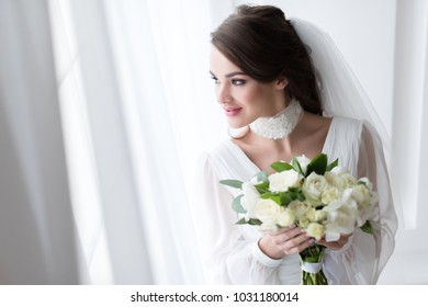 smiling bride in wedding dress and veil holding white bouquet