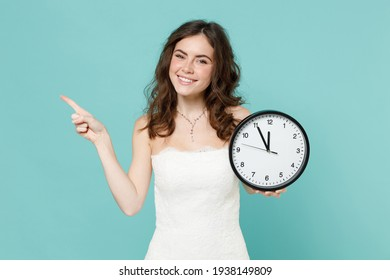 Smiling bride young woman 20s in beautiful white wedding dress hold clock pointing index finger aside isolated on blue turquoise color background studio portrait. Ceremony celebration party concept