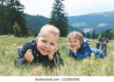 smiling brother and sister laying on grass