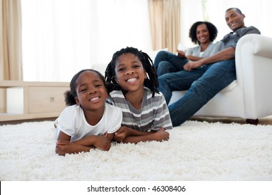 Smiling brother and sister lying on the floor  in the living room