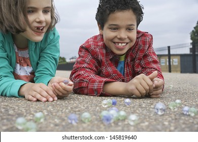 Smiling brother and sister playing marbles on playground