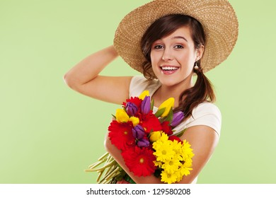 Smiling brunet woman with hat and spring flower