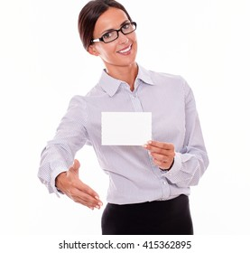 Smiling brunette businesswoman with glasses, wearing her long hair tied back, and a button down shirt, holding a blank copy space in one hand, with the other hand out in a greeting gesture
