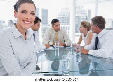 Smiling brunette businesswoman in a meeting with colleagues working behind