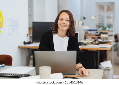Smiling brunette businesswoman portrait in office sitting at the desk behind open laptop, looking at camera and smiling with friendly face, as if greeting a client. Front half-length portrait