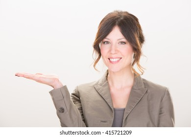 smiling brunette businesswoman show product isolated on grey