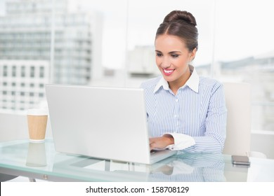 Smiling brunette businesswoman typing on laptop in bright office