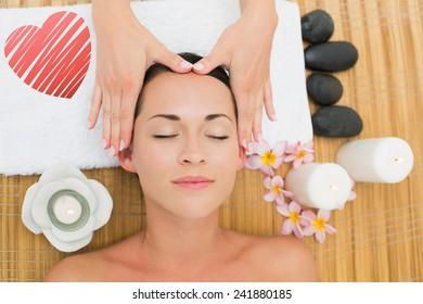 Smiling brunette enjoying a head massage against red heart