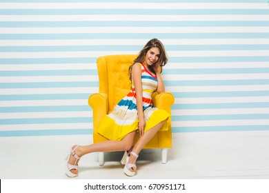 Smiling brunette girl in bright summer dress posing indoors, sitting in big yellow armchair. Portrait of gorgeous young woman with light-brown hair resting in her room on striped background.