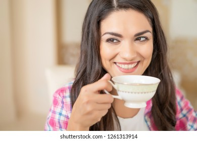 Smiling Brunette Girl Drinks A Coffee From A Cup In A Restaurant While Looking Sideways And Flirting