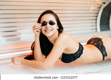 smiling brunette girl lies in a sunroom, wants a beautiful even tan, in goggles