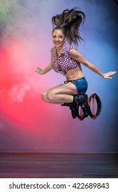 Smiling brunette girl with long hair  jumping in  kangoo jumps shoes