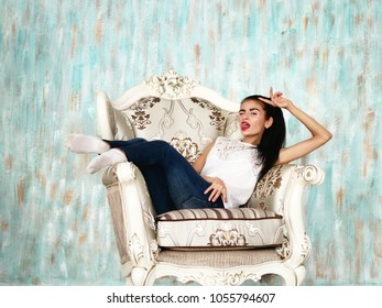 Smiling brunette girl posing indoors, sitting in big armchair. Portrait of gorgeous young woman with emotions on face.