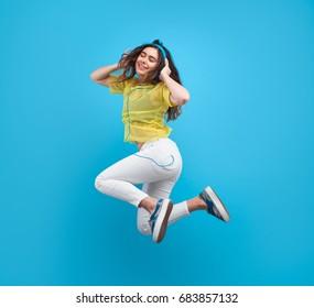 Smiling brunette girl wearing headphones enjoying music jumping with eyes closed against blue background.