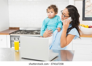 Smiling brunette holding her baby and using laptop on phone call in the kitchen