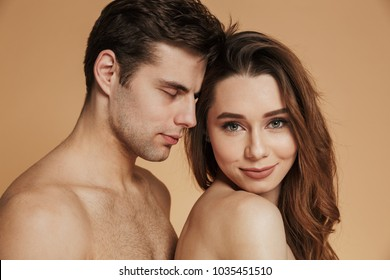 Smiling brunette lady looking camera and smiling while standing near shirtless man isolated over beige