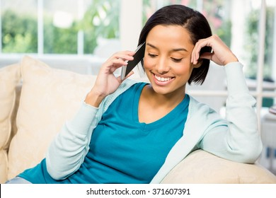 Smiling brunette on a phone call while sitting on the sofa