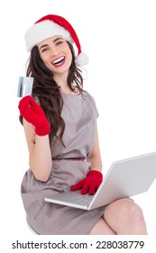 Smiling brunette shopping online with laptop on white background
