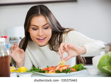 Smiling brunette woman decorating prepared shrimps on plate in kitchen