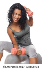 Smiling brunette woman in grey sportswear sits on fitness ball and holds small dumbells.