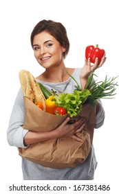 Smiling  brunette woman with grocery bag full of fresh vegetables and red paprika