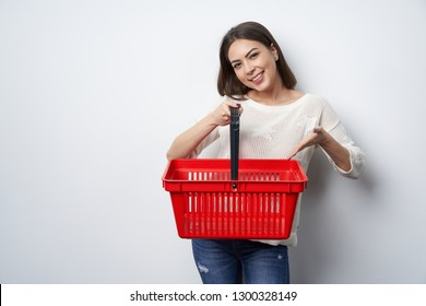 Smiling brunette woman holding empty shopping basket pointing in it, looking at camera smiling