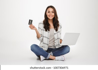 Smiling brunette woman in shirt sitting on the floor with laptop computer and credit card while looking at the camera over gray background