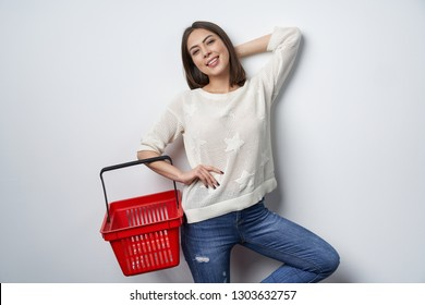 Smiling brunette woman standing by white wall posing holding empty shopping basket, looking at camera smiling
