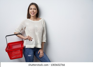 Smiling brunette woman standing by white wall holding empty shopping basket, looking at camera smiling