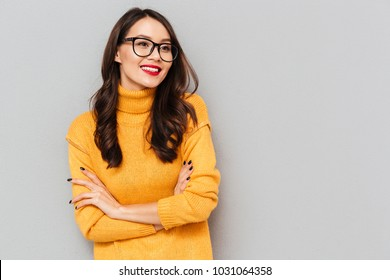Smiling brunette woman in sweater and eyeglasses with crossed arms looking away over gray background