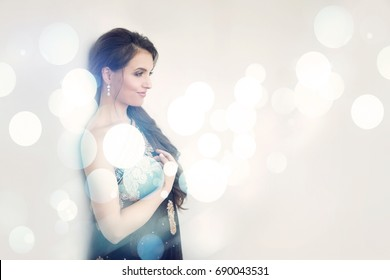 Smiling brunette woman in traditional luxury indian black dress wearing diamond earrings in white blue lights on background. Holidays, christmas, wedding, celebration concept. Happy positive emotions