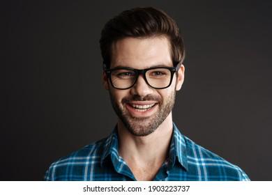 Smiling brutal guy in eyeglasses posing on camera isolated over black background