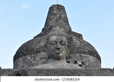 smiling buddha statue at borobudur temple