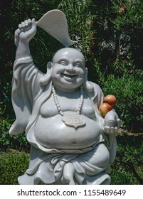 A smiling buddha statue with a pair of apples for an offering held in its arms.
