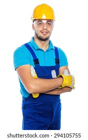 Smiling builder with crossed arms in a protective blue clothing isolated on white background. Young construction worker holding hardhat or yellow helmet.