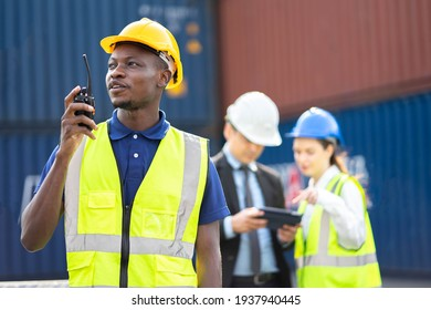 Smiling builder Engineering in hardhat with walkie talkie over group of builders at construction site.