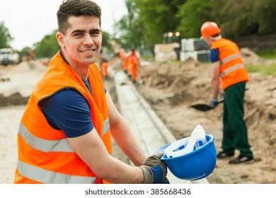 Smiling building worker holding helmet in hand