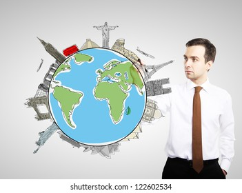 smiling businesman drawing colorized earth, traveling concept