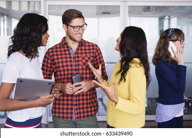 Smiling business colleagues talking while standing in office