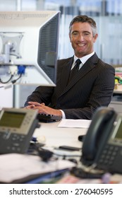 Smiling business executive dressed in black, sitting in front of a computer.