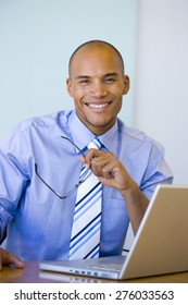 Smiling business executive with laptop.