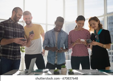 Smiling business executives using mobile phone in office