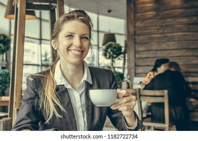 smiling business lady drinks coffee in a cafe. young businesswoman on a coffee break.