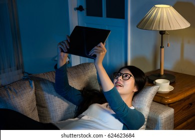 smiling business lady watching famous video movie holding pad computer up lying on the couch at night near lamp in the vacation evening relaxing without all work thing.