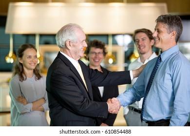 Smiling Business Leader Congratulating Colleague