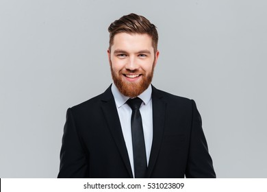 Smiling business man in black suit with tie in studio looking at camera. Isolated gray background