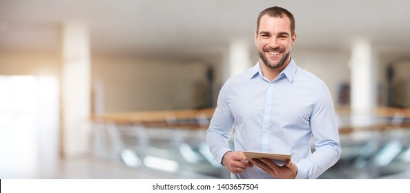 Smiling business man in the business center with tablet