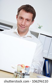 Smiling business man at desk with laptop in the office